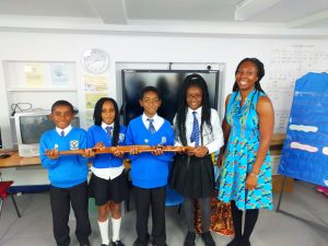 Year 5 pupils holding an African staff with Wendy Shearer - Storyteller